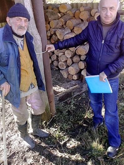 KOHTAKTbI kauft für bedürftige NS-Opfer im Kaukasus immer Brennholz für den Winter. Unser georgischer Partner Nugsar Andguladse (rechts) mit Herrn Akaki Koridse vor einem Holzstapel.