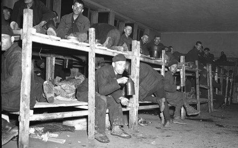 """34317 28 APR 45 U.S. Army Signal Corps Fotograf CPL J.D.Karr Inneres eines """"Krankenhaus""""zimmers im deutschen Kriegsgefangenenlager, das von der 75. Infanteriedivision, 9. U.S. Armee eingenommen wurde, in Hemer, Deutschland. Hier lagen Männer, einige mit TB, ohne irgendwelche Decken. In diesem Lager mit 22.000 Männern, waren 9.000 Krankenhausinsassen. Die meisten Gefangenen waren Russen."""